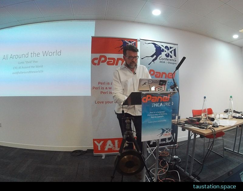 Curtis at a standing desk, looking at his laptop. On the left side his slides are projected for the audience