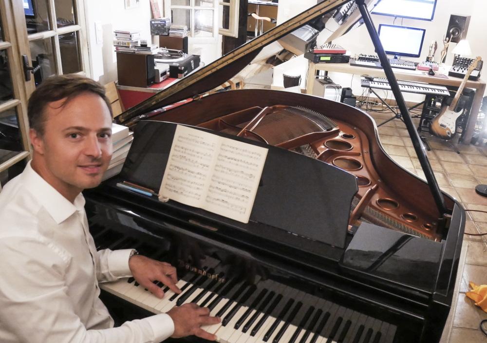 Luke Corradine in his studio, playing piano